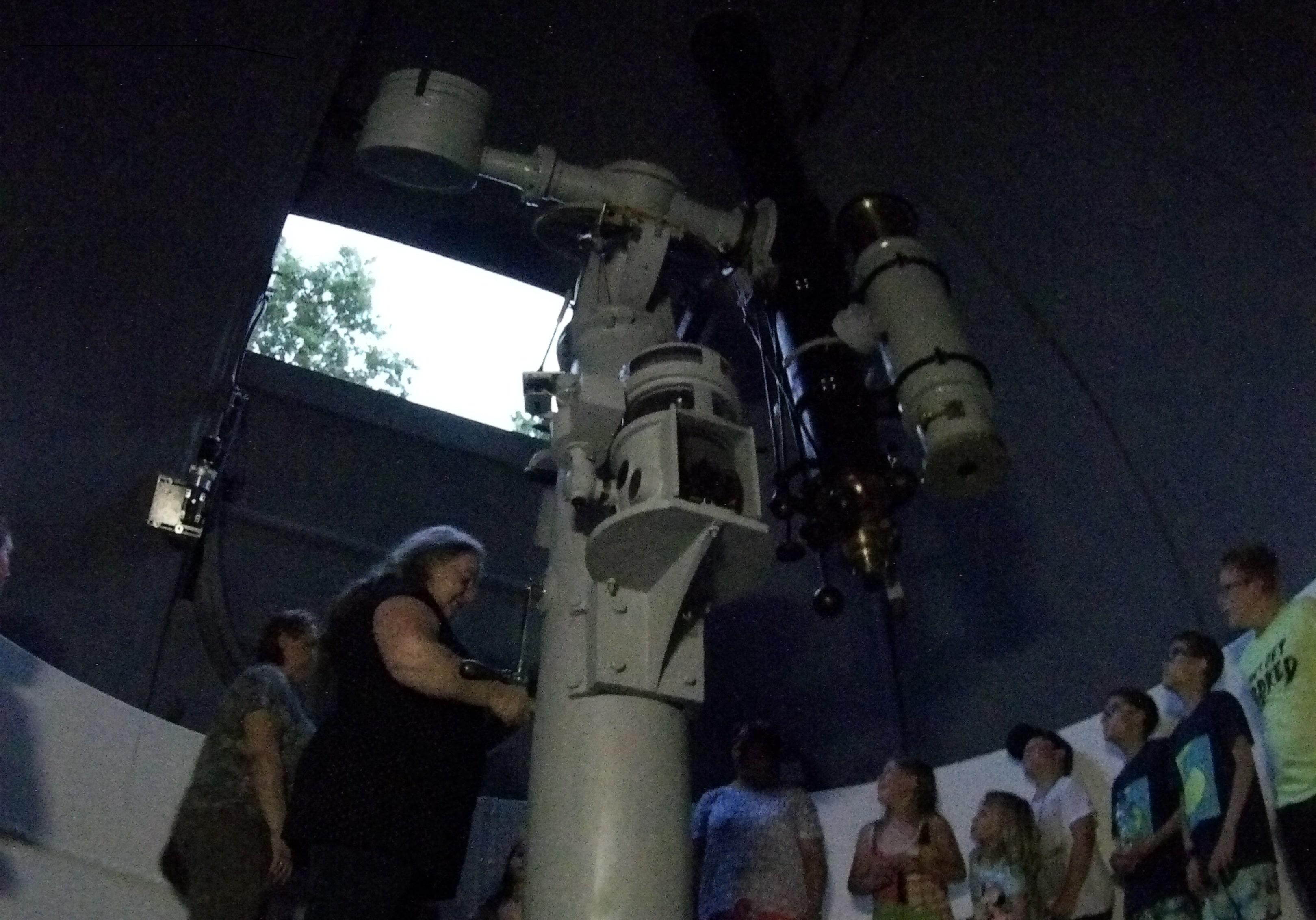 Pani astronom opowiada o teleskopie. Demonstruje działanie kopuły.