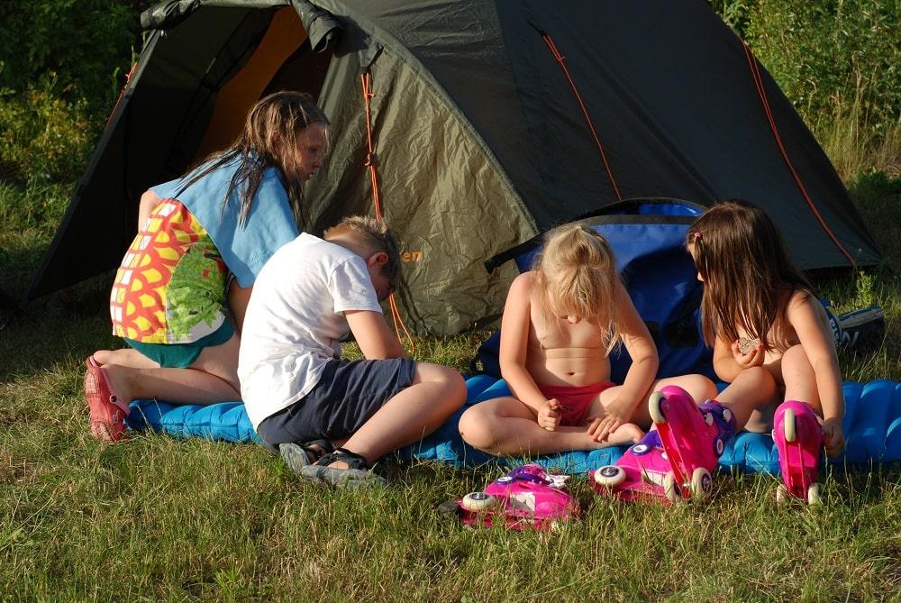 Dzieci siedzące przed namiotem.