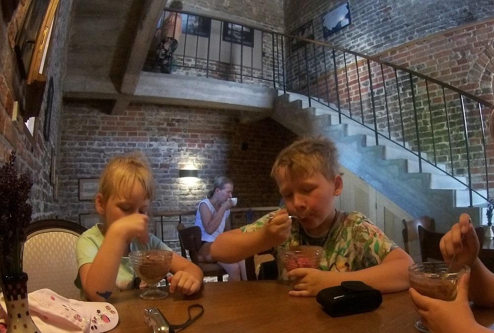 Piętro kawiarni w Wieży Wodnej. Dzieci jedzą lody w tle kobieta pije kawę.