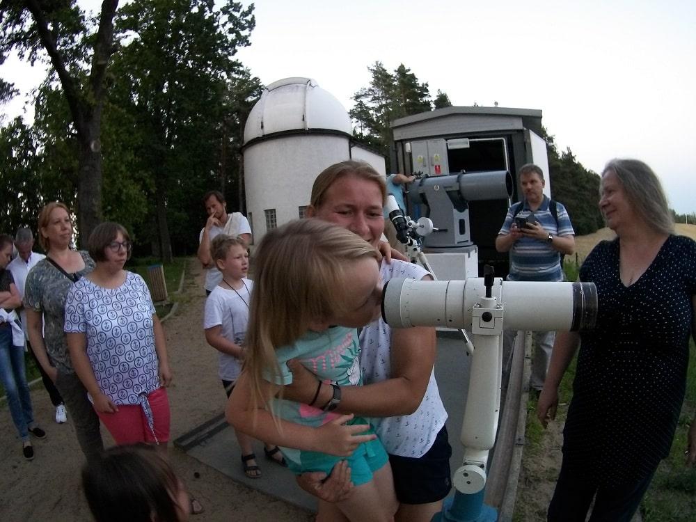 Mama z córką obserwują okolice przez lunetę.