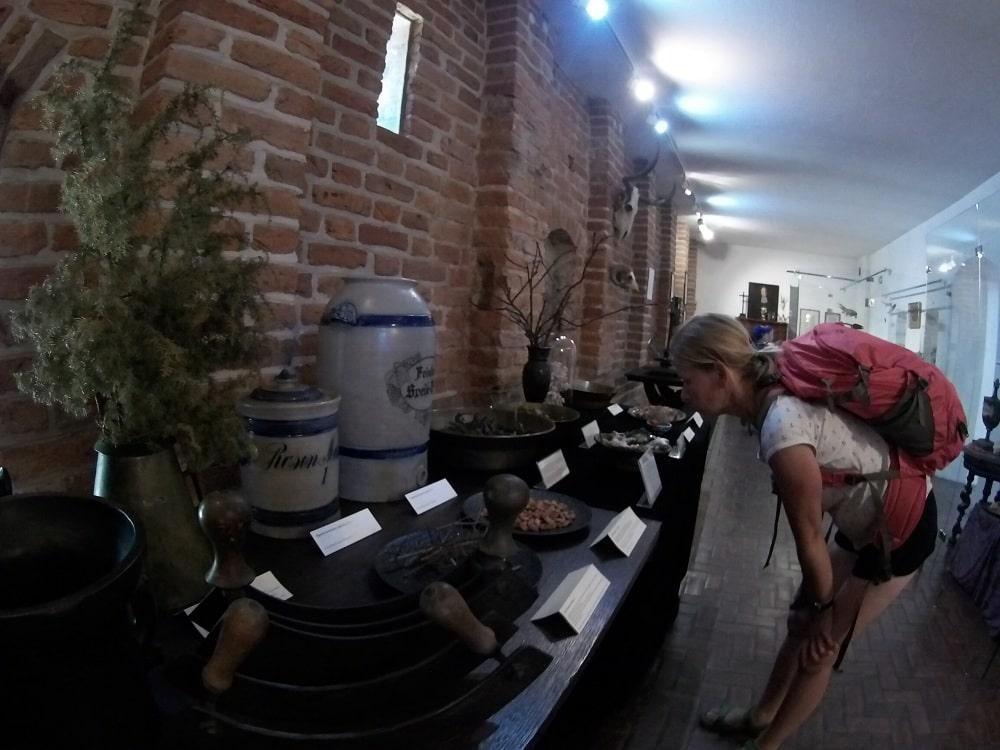 Kobieta ogląda wystawę ziół i naczyń aptekarskich