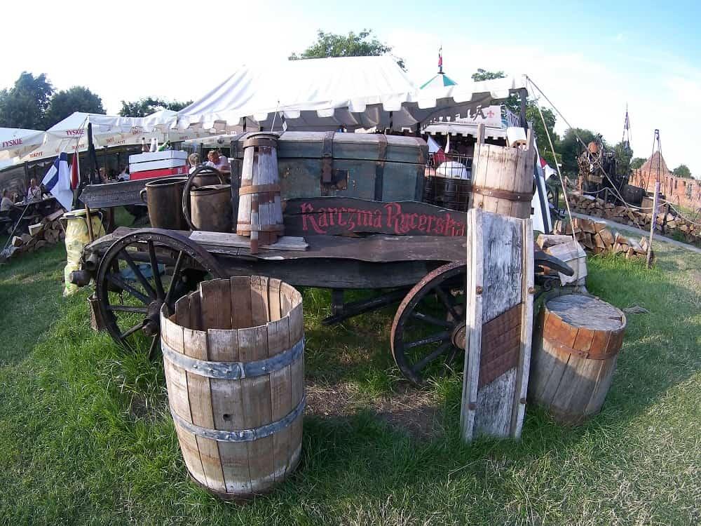 karczma rycerska pod zamkiem w Malborku. Stary wóz, beczki, w tyle namiot gdzie wydają jedzenie.