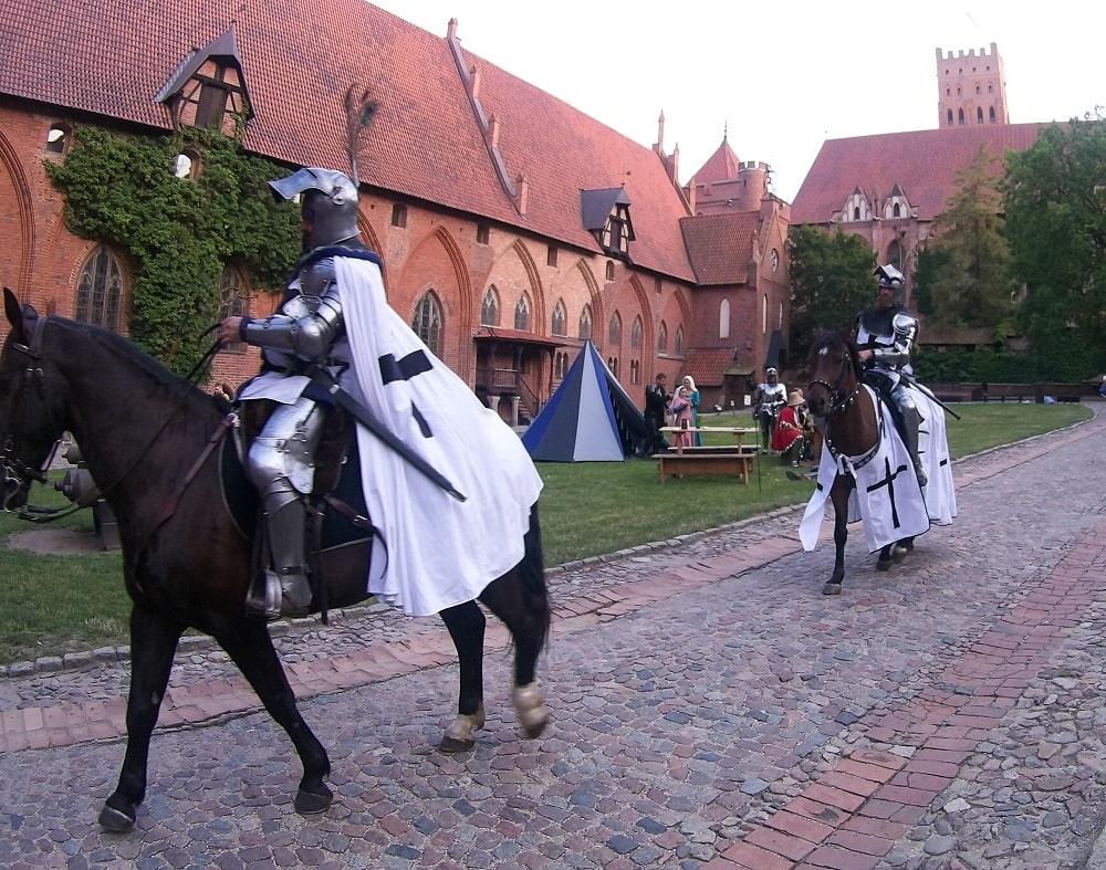 Rycerze zakonu na koniach przemierzają dziedziniec zamku średniego