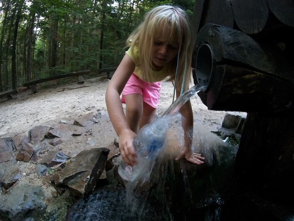 Dziewczynka napełnia wodą ze źródła św. Franciszka butelkę. Woda rozbryzguje się na boki.