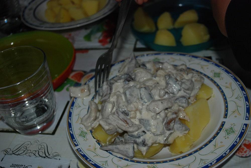 Kartofle z grzybami, na talerzu. obok pusta już szklanka w której dopiero co było wino.