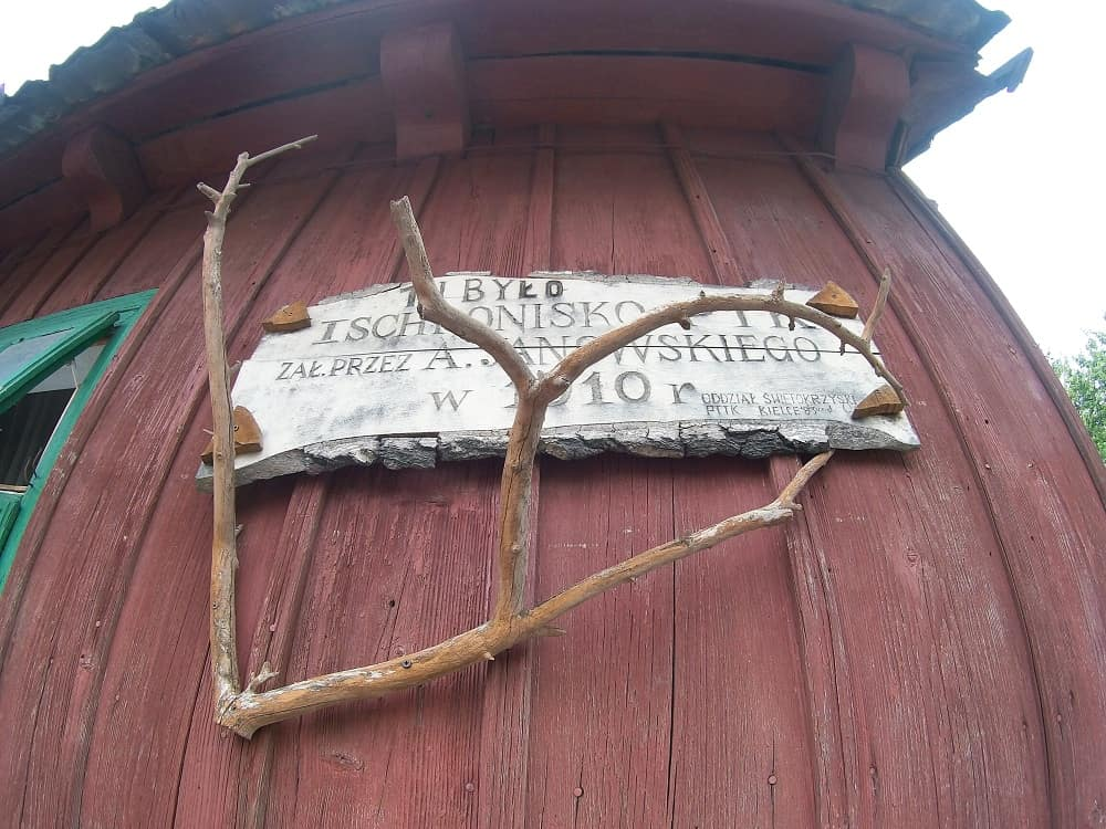 Na drewnianej ścianie tablica też drewniana obwieszczająca, że było tu pierwsze schronisko w Górach Świętokrzyskich