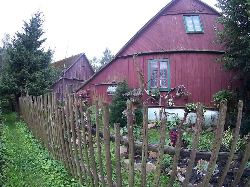 Płot drewniany na pierwszym planie. Mały ogródek za płotem, w tle drewniane zabudowania.