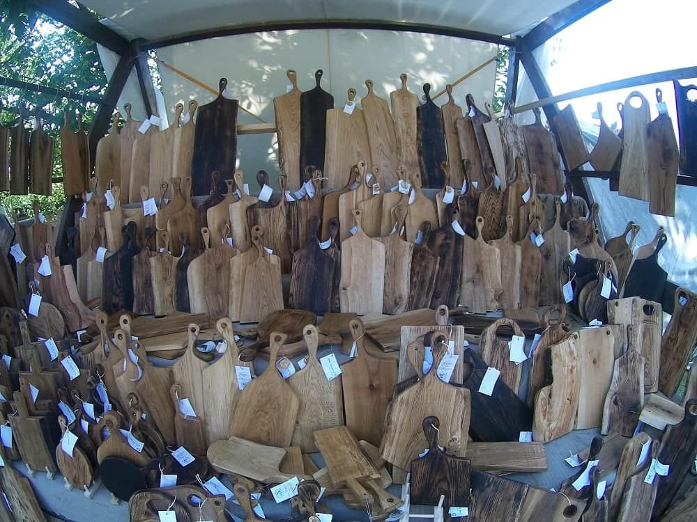 Deski do krojenie wystawione na straganie. Deski te wykonane są z różnego rodzaju drewna i różnych kształtów, ustawione jedna przy drugiej.