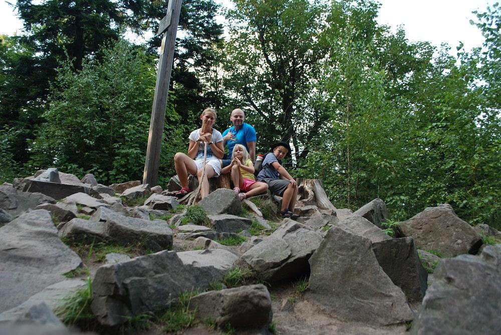 Rodzina siedzi na kamieniach na szczycie Łysicy.