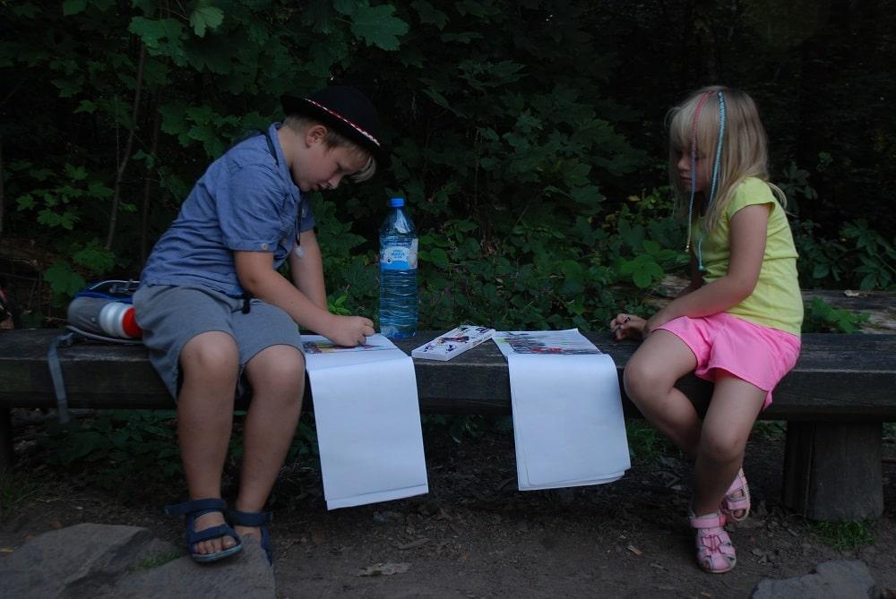 chłopiec lat 8 i dziewczynka lat 6 siedzą na ławce i rysują w swoich blokach.
