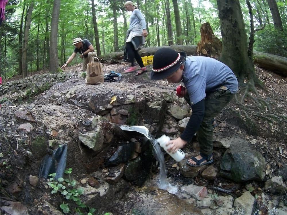 Chłopiec nabiera wody ze źródełka do bidonu