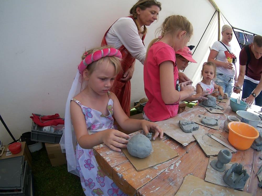 Dzieci pod okiem instruktorki lepią dzieła w glinie.Zuzia na pierwszym planie z wielką kulą gliny