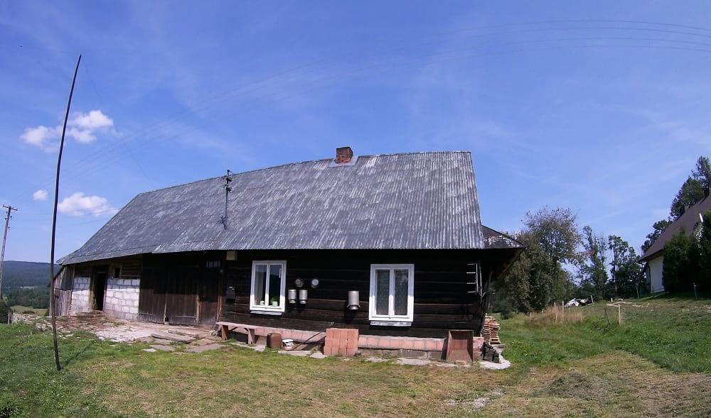 Budynek drewniany, połączony z pomieszczeniami gospodarczymi. Na domu pomiędzy oknami wiszą kany na mleko.