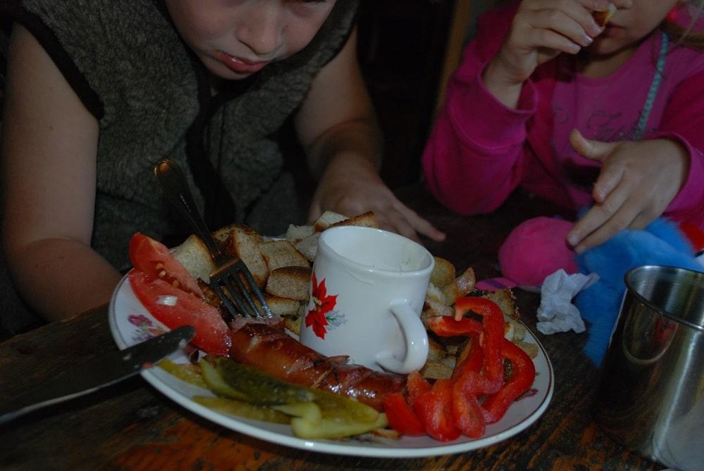 Chłopiec, dziewczynka. Przed nimi talerz ze smażoną kiełbasą, papryka,pokrojone ogórki kiszone, pomidory i grzanki.anie bacówkowe.