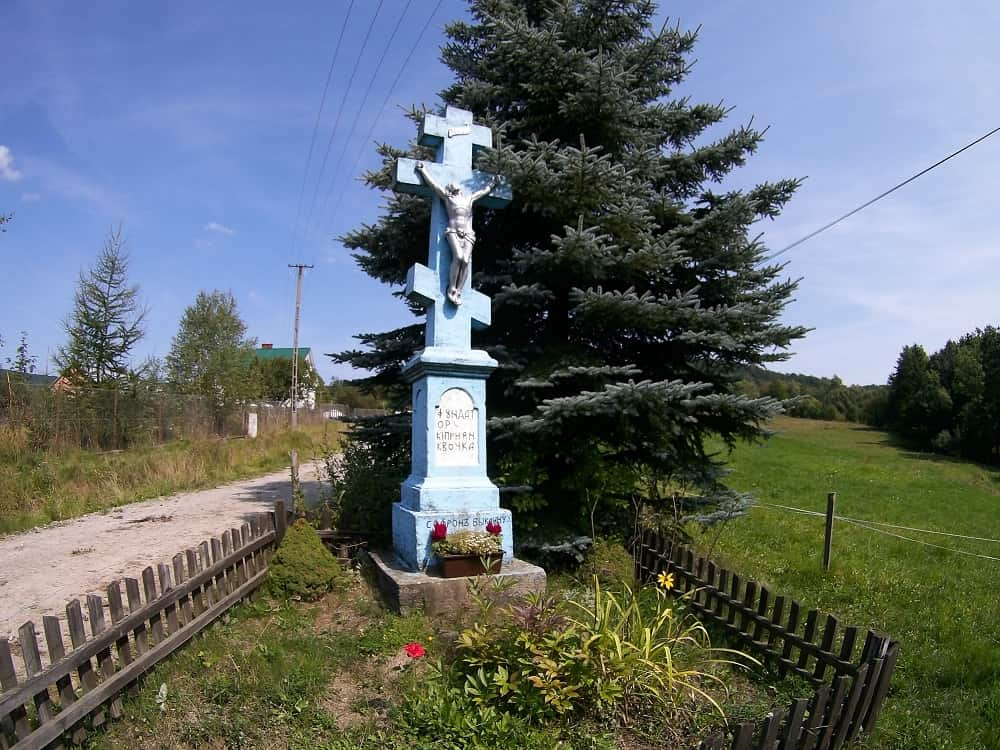 Krzyż o ośmiu końcach i trzech poprzeczkach wykonany z kamienia. na krzyżu postać Jezusa. Krzyż otoczony jest drewnianym płotkiem.