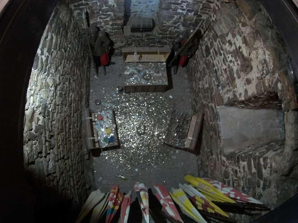 Kamienna piwnica, w niej skrzynie, monety, flagi.