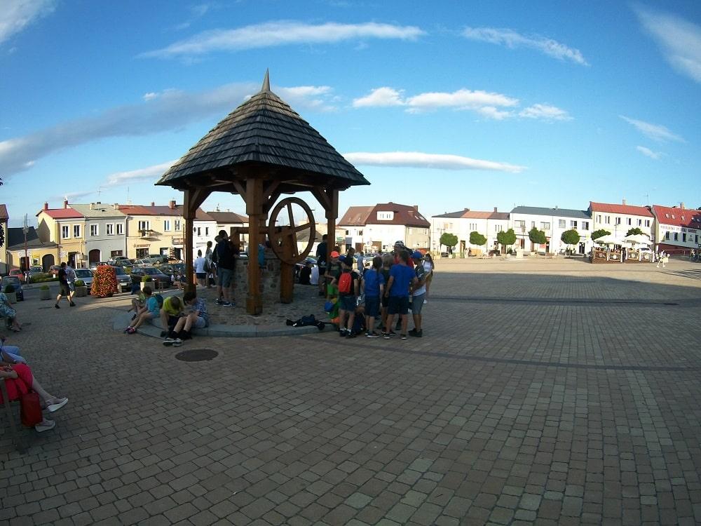 Duży kwadratowy plac jeden z dawniejszych rynków w miasteczku. W tyle zdjęcia zabudowania mieszkalne, stare kamienice. W centrum zdjęcia studnia.