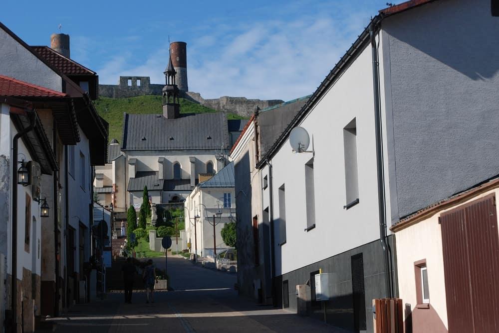 Ulica Łokietka prowadzi do kościoła, który widać na jej końcu. Za kościołem na zielonym wzgórzu ruiny zamku, dwie okrągłe wierze zakończone czerwoną cegłą.
