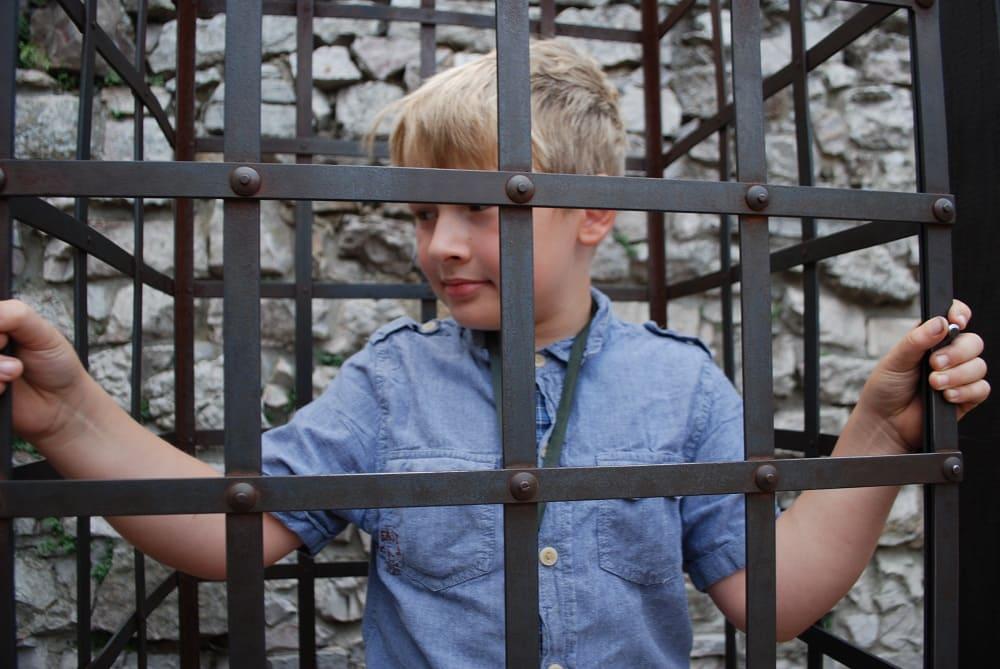 Chłopiec w metalowej klatce.