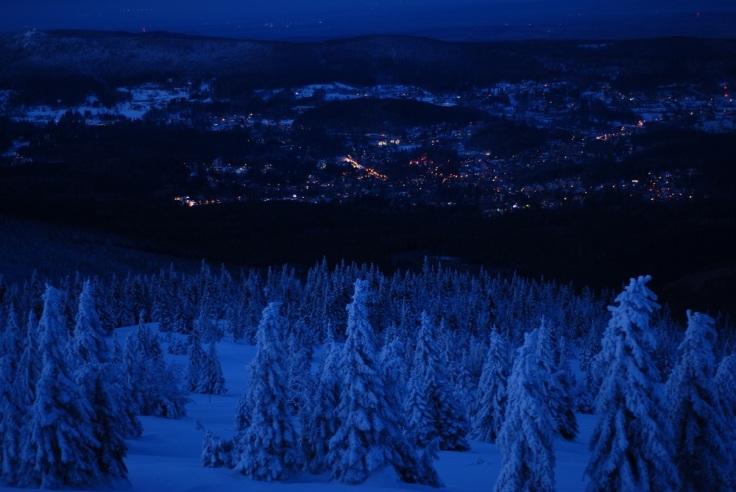 Widok z pod Łabskiego szczytu. ośnieżone choinki a w dole światła miasta