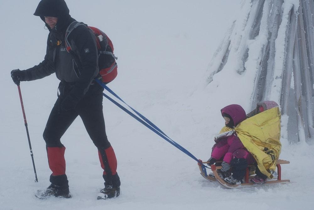 Mężczyzna z plecakiem ciągnie sanki z dwiema dziewczynkami. Jest zimno i wieje. Dziewczynki okryte są Nrc-tą