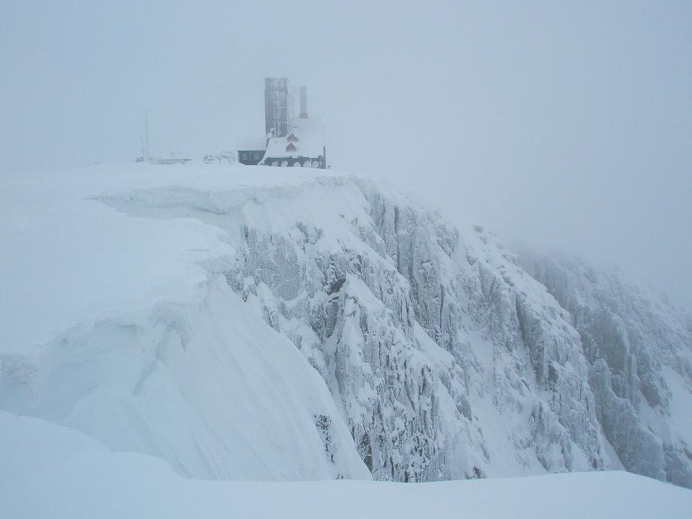 Ośnieżony krajobraz. na pierwszym planie strome ściany śnieżnych kotłów, miejsca przytulnego wspinaczom. Na skraju kotłów budynek z wieżą, dawniej to było schronisko