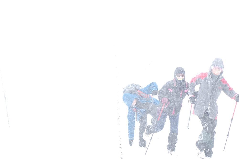 Trójka turystów zmagająca się z wiatrem. Trzy postacie ledwie wyłaniają się z bieli