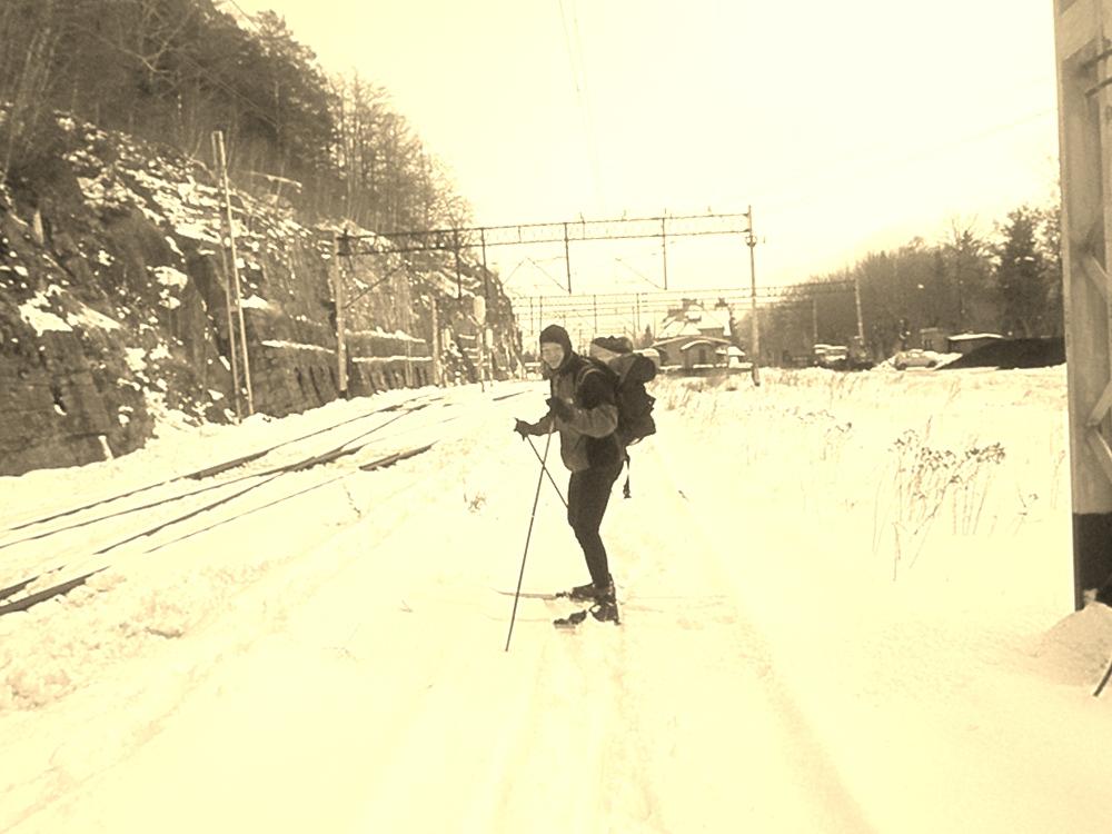 Zdjęcie w sepii. Narciarz biegowy z plecakiem na tle stacji szklarska Poręba