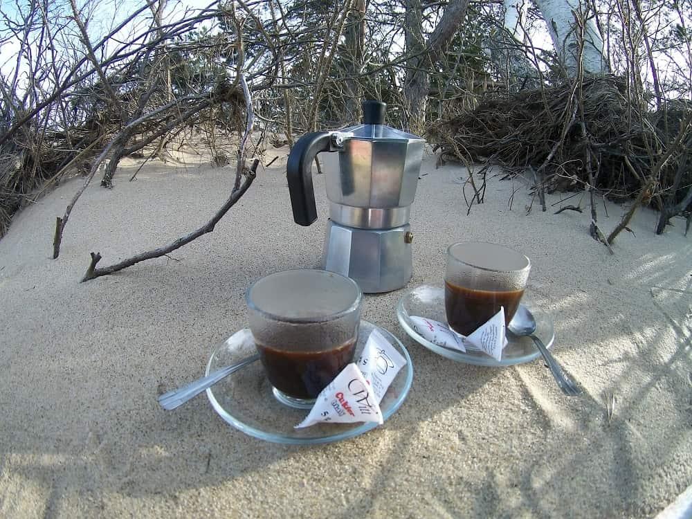 Kawiarka i dwie filiżanki z mocną kawą. Wszystko to stoi na piasku. w tle suche gałązie.