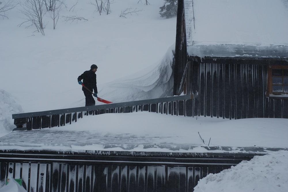 Mężczyzna oczyszcza dachy schroniska ze śniegu