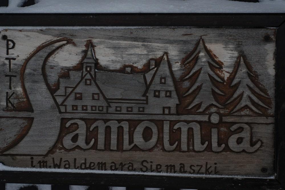 Drewniana tablica z ryciną budynku i napisem Samotnia im. Waldemara Siemiaszki