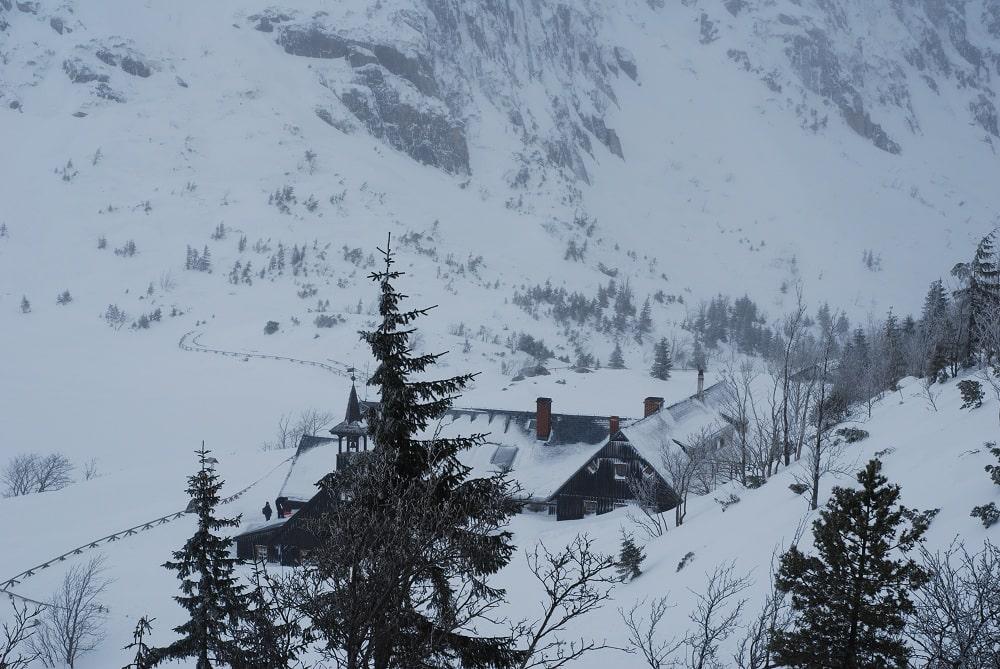 Widok schroniska PTTK Samotnia od strony szlaku z góry. Wdać charakterystyczną wieżyczkę. Na pierwszym planie choinki w tle zarys Małego Stawu skutego lodem.