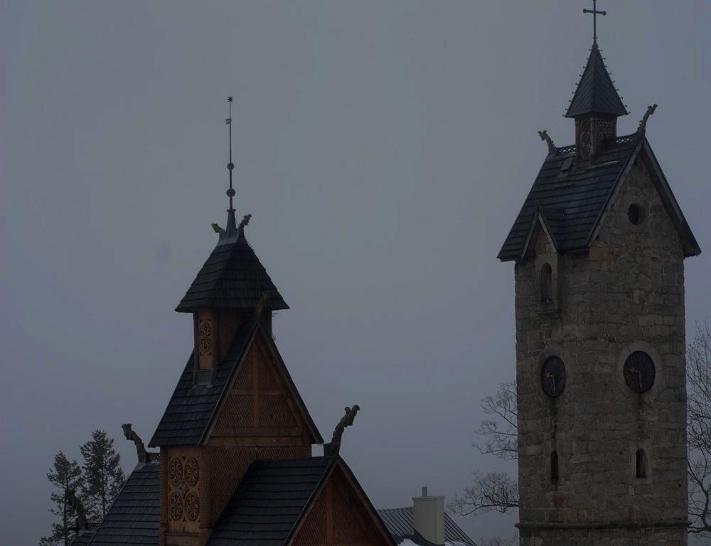 Po lewej kamienna wieża z zegarem wskazującym 21.30, która chroni świątynię przed kaprysami Ducha Gór. Po lewej, jakby na dalszym planie, drewniana świątynia z charakterystycznymi zdobieniami. wszystko pogrążone w mroku/
